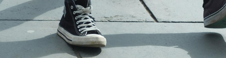 Piernas y zapatillas de 2 jóvenes caminando en una acera