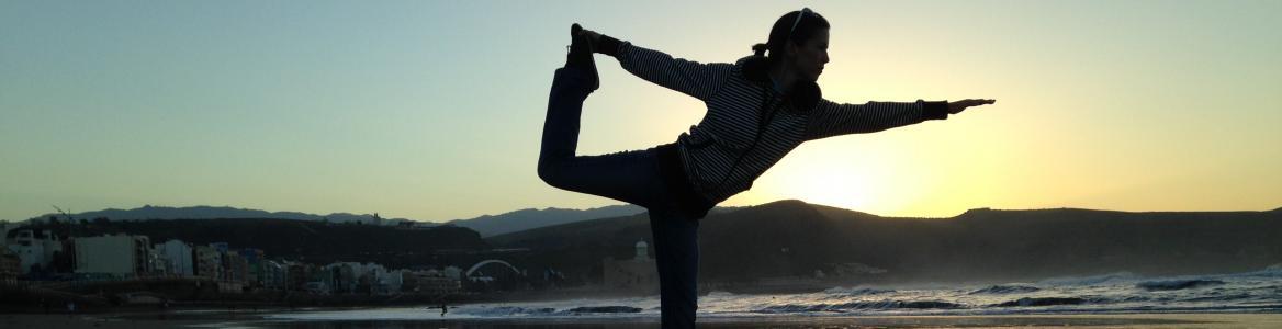 Vista de una mujer haciendo yoga en la playa