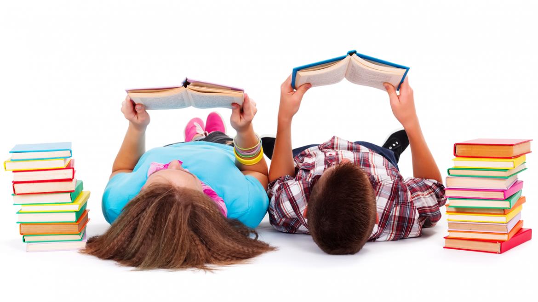Niños tumbados en el suelo leyendo