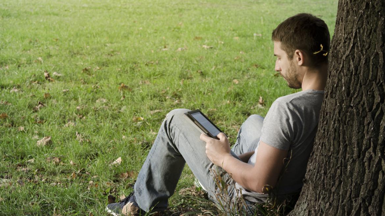 Chico leyendo en una tableta y apoyado en un árbol
