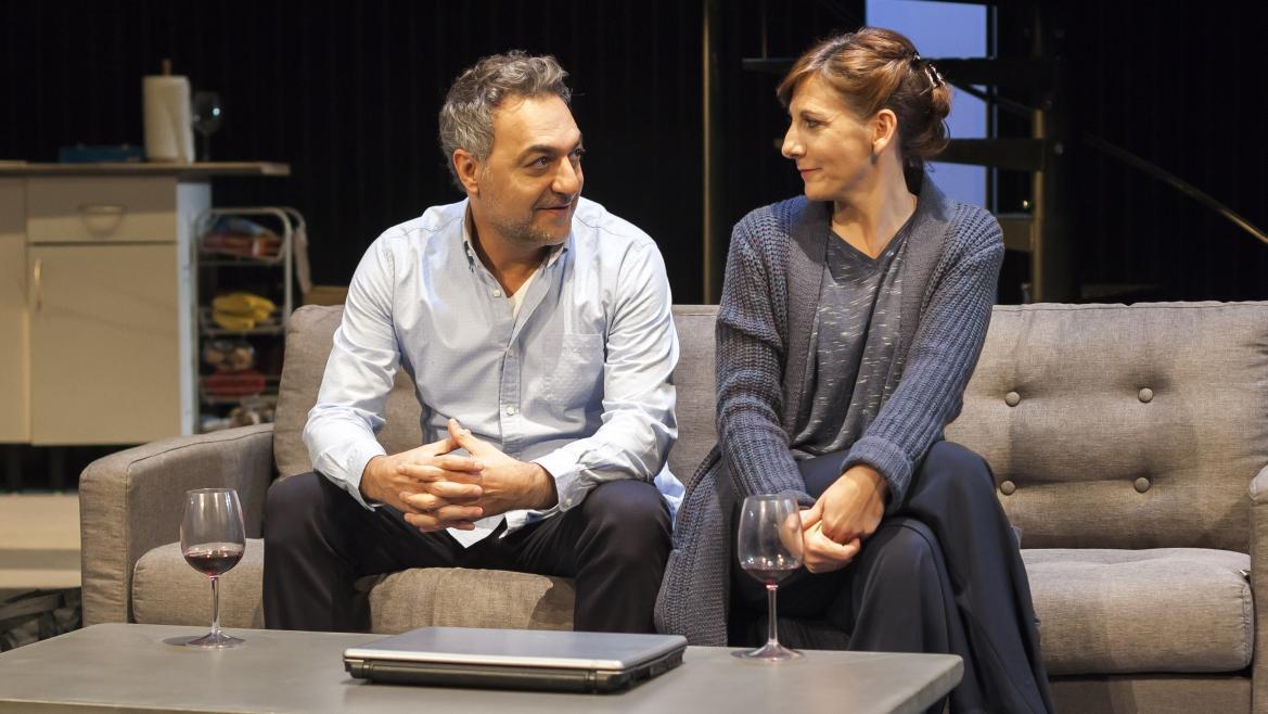 Obra de teatro. Una pareja sentada en un sofá con una copa de vino