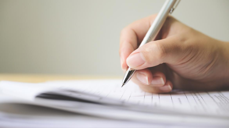 Mano con un bolígrafo firmando unos papeles