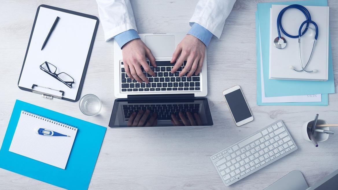 profesional sanitario escribiendo en ordenador portátil