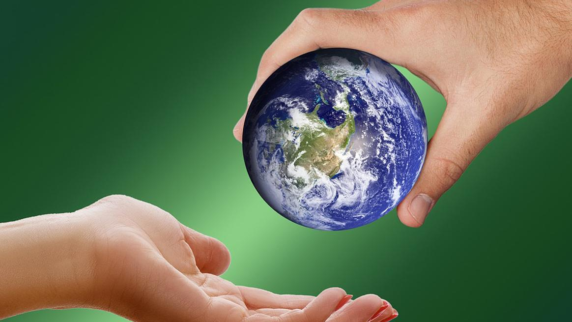 Una mano tiende simbólicamente el mundo a otra