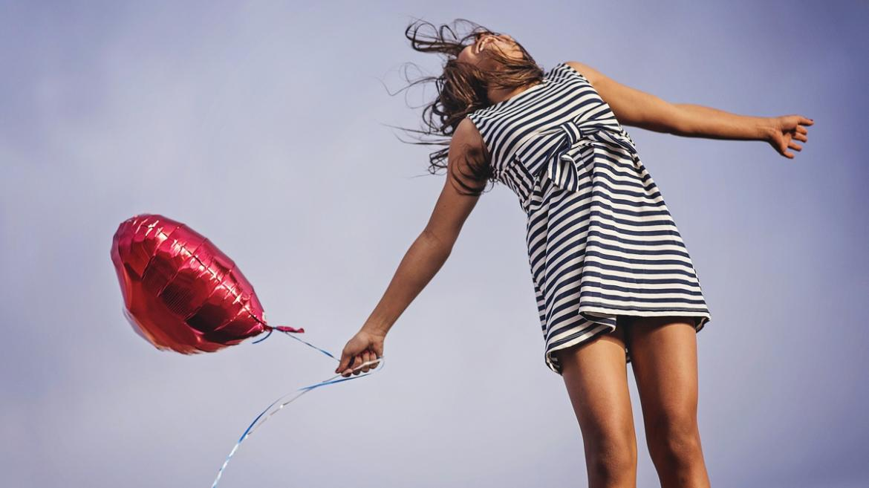 Mujer feliz con un globo en la mano