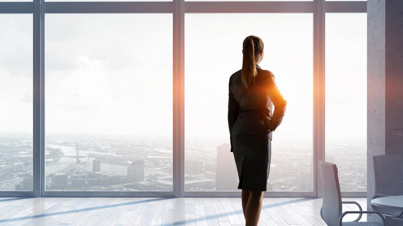 Mujer mirando hacia un ventanal dentro de una oficina