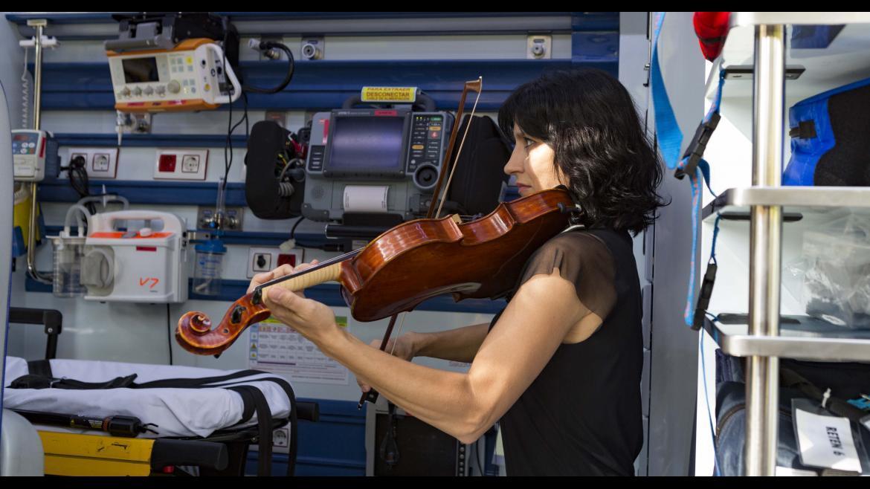 Una violinista de la ORCAM interpreta una pieza musical en el interior de una UVI del SUMMA 112