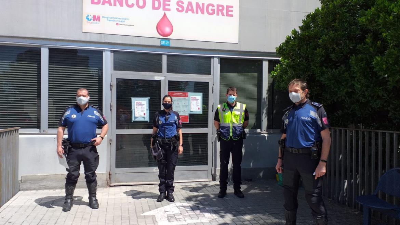 Cuatro policías municipales delante de un Banco de sangre