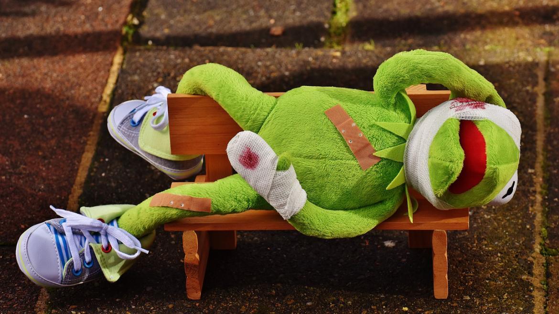Imagen decorativa de un muñeco rana con heridas