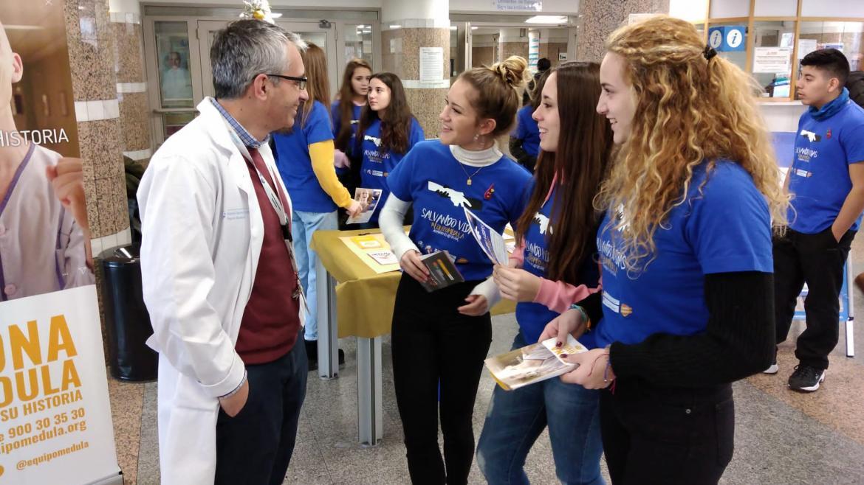 Alumnos con un profesional médico mientras pormocionan la donación de médula