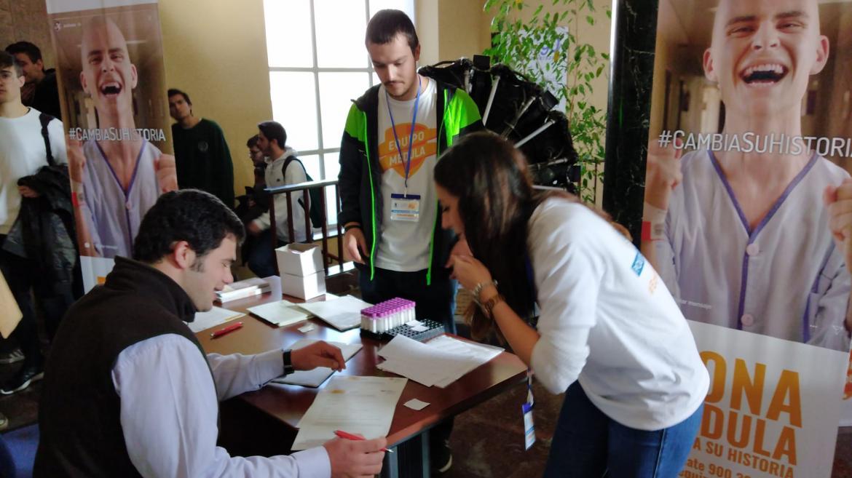 jóvenes sentados informándose sobre el registro como donante de médula