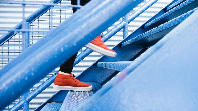 Muestra los pies de una persona subiendo escaleras