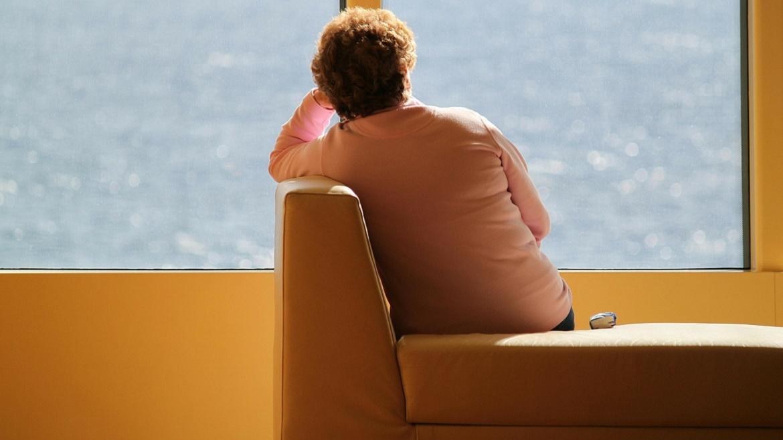 Mujer sentada mirando al infinito por un ventanal