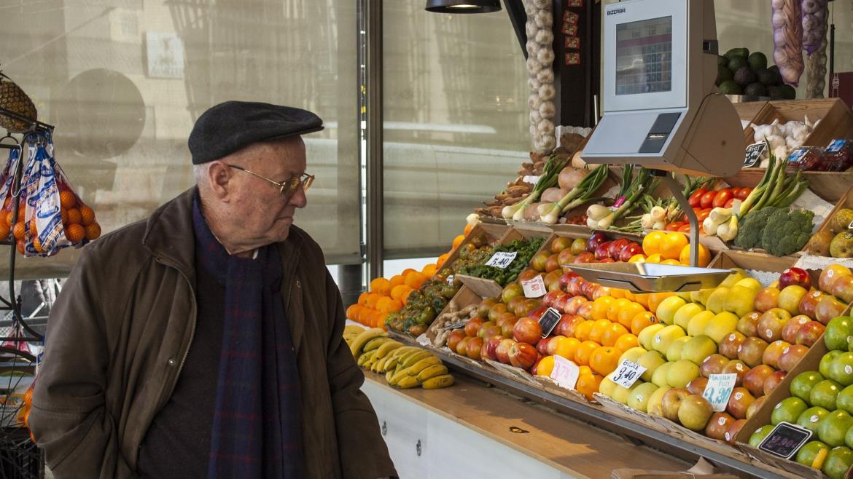 Señor mayor comprando en un puesto de fruta