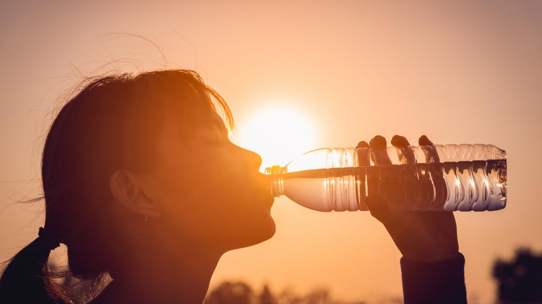 Una joven se refresca bebiendo de una botella de agua