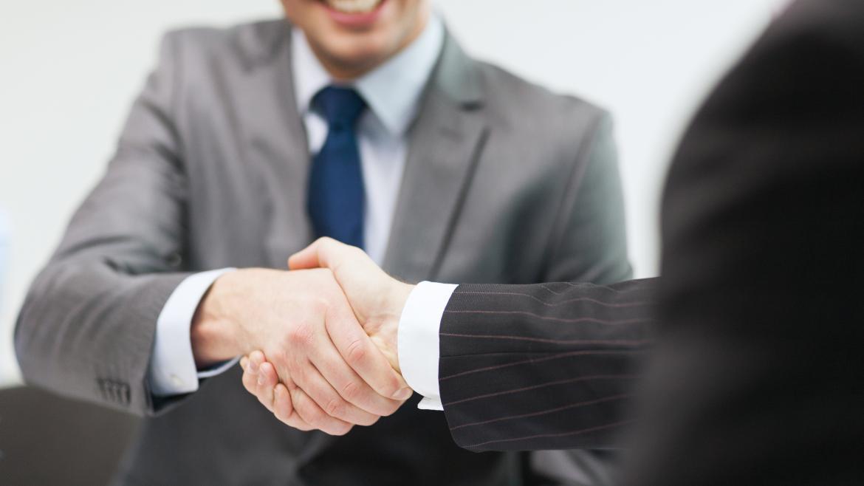 Dos hombres sellan un acuerdo con un apretón de manos