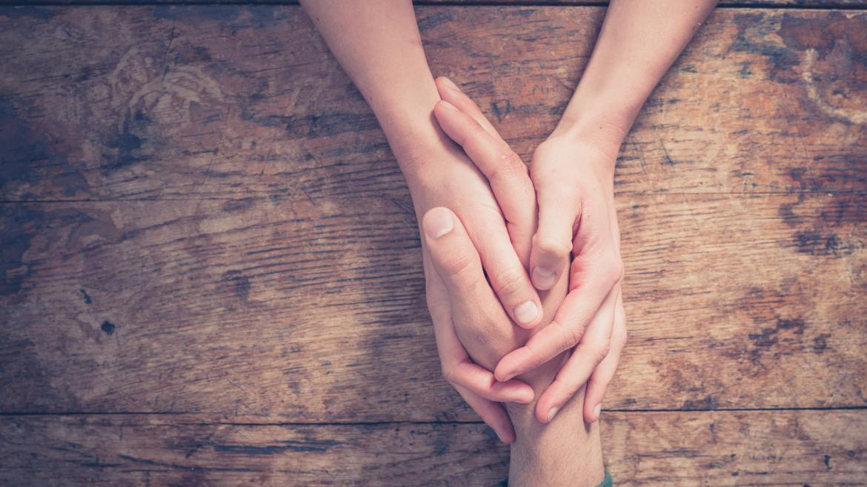 una persona coge y protege  la mano de otra sobre una mesa