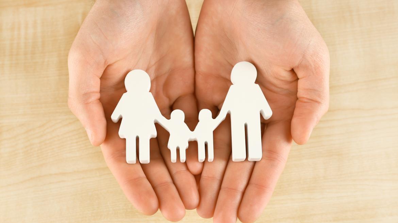 Unas manos sujetan unas figuras de papel representando a una familia