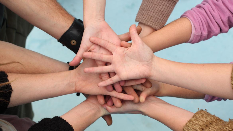 Un grupo de manos juntas