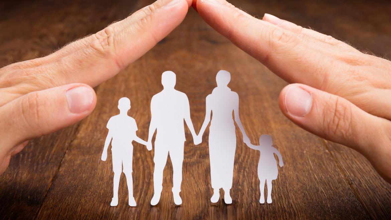 Dos manos cubren un recorte de papel representando una familia