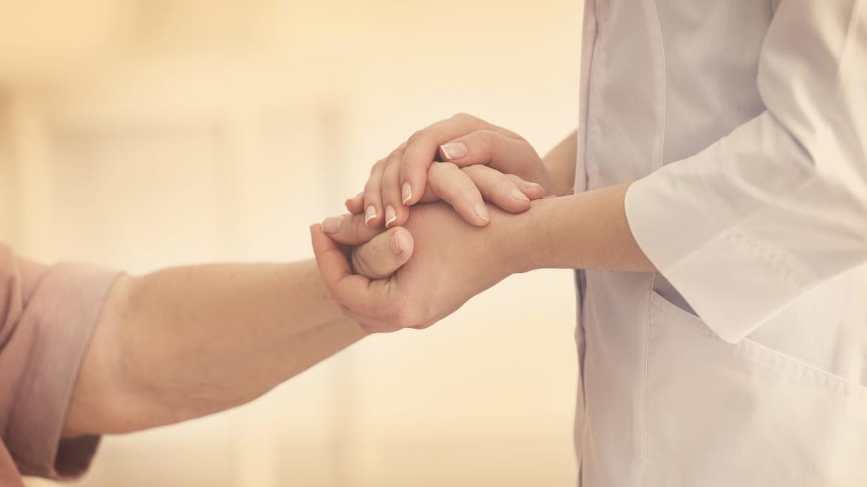 Una doctora coge las manos de una paciente