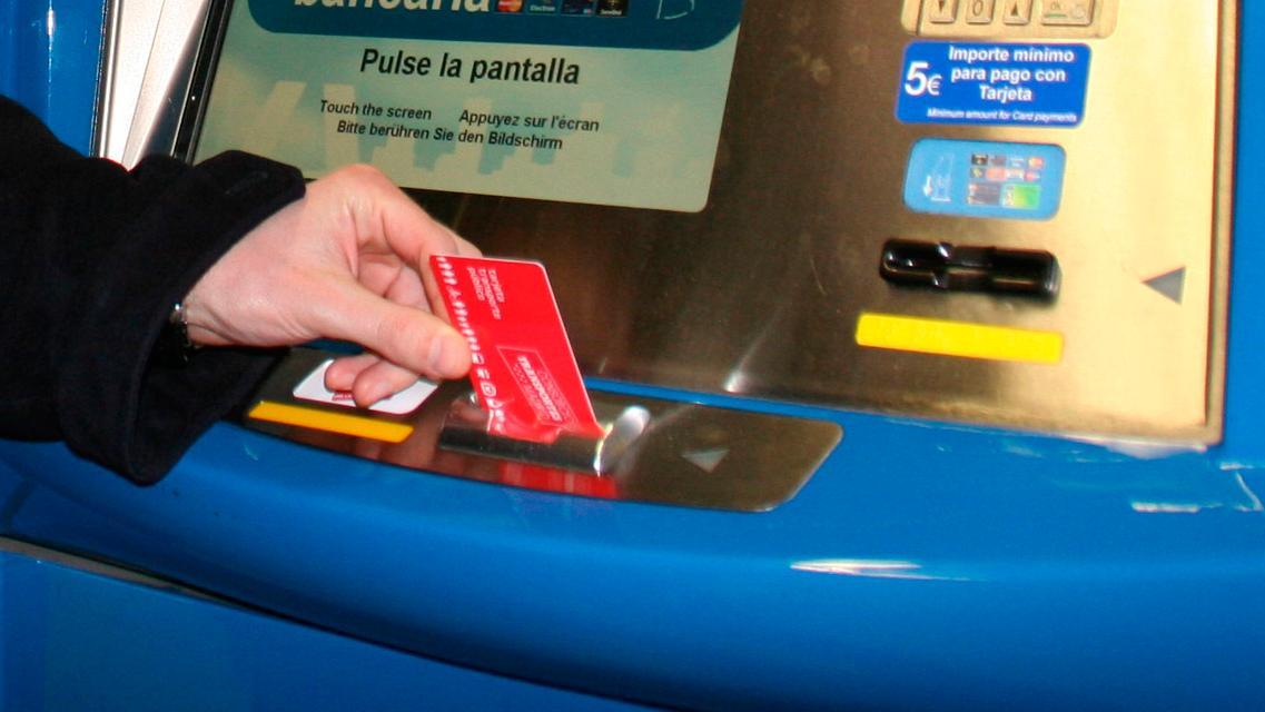 Mano introduciendo una tarjeta transporte público en una máquina  expendedora de títulos
