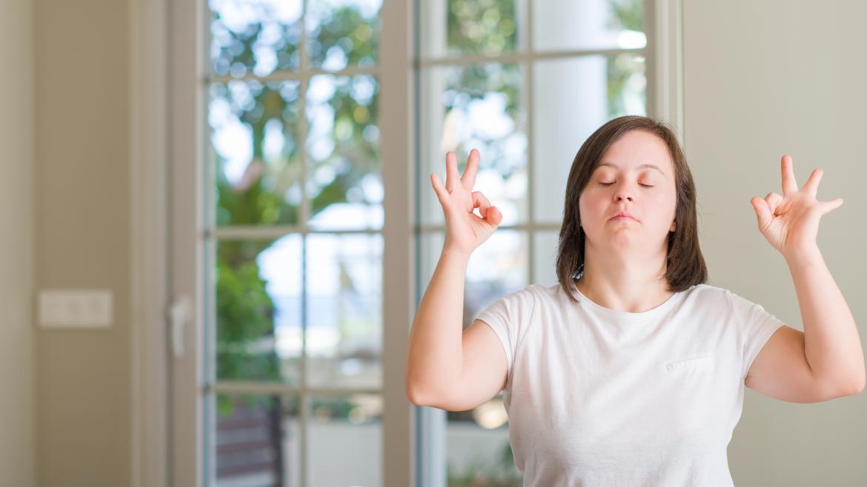 Mujer con síndrome de down haciendo meditación