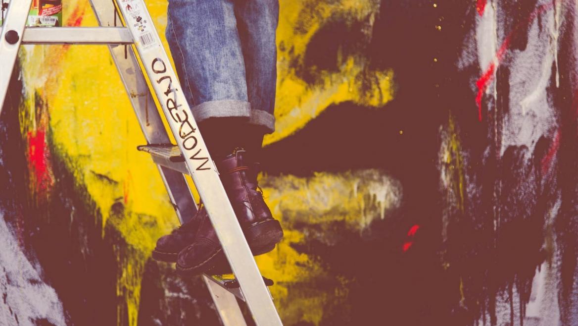 Joven subido en escalera ante un mural