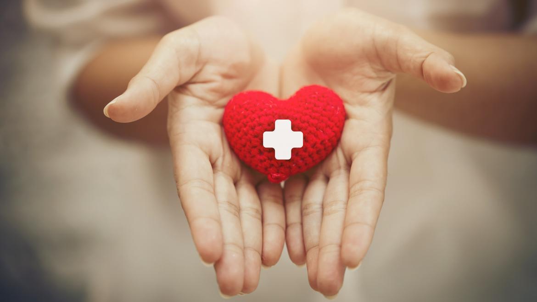 Manos con un corazón rojo y una cruz blanca