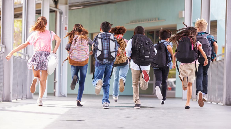 Niños con sus mochilas corriendo por un pasillo