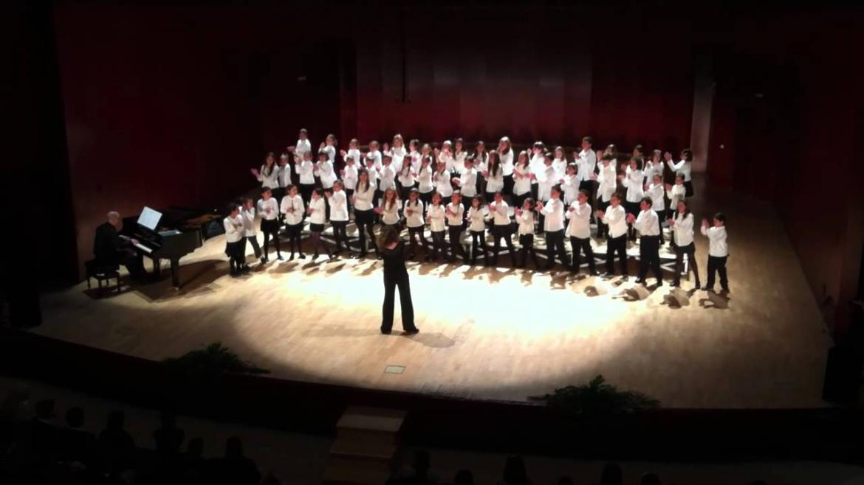 Coro de niños cantando sobre un escenario