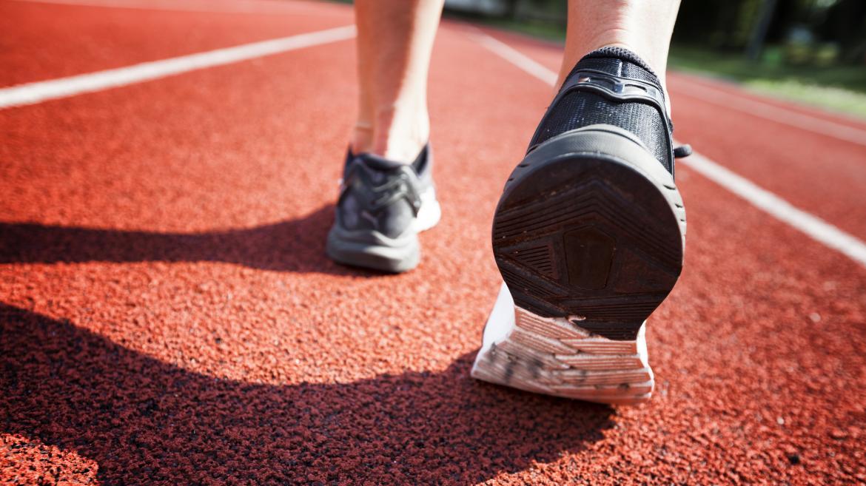 Persona andando en pista de atletismo