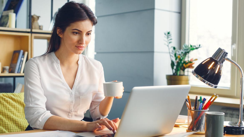 Mujer trabajando con un ordenador desde su casa