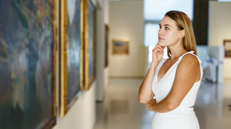 Mujer contemplando un cuadro en un museo de pinturas