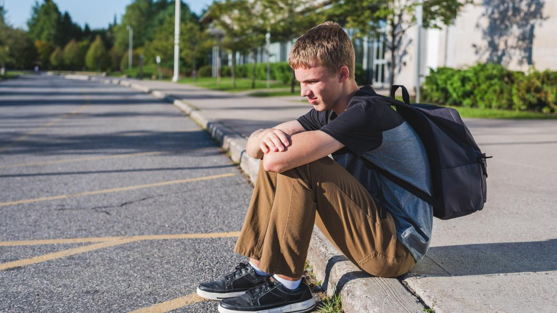 Estudiante con una mochila ed libros a la espalda, sentado en la calle