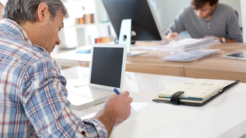 Un joven y un señor mayor estudiando cada uno con su ordenador