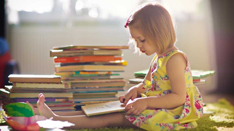 Niña sentada en el suelo con una pila de libros, leyendo