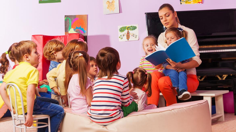 Niños en una clase de educación infantil sentado en el suelo alrededor de la profesora que está leyendo un libro