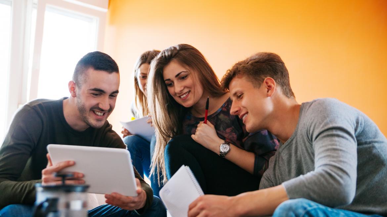 Un joven muestra a otros jovenes una tablet con algo que les hace felices