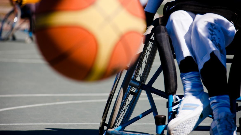 Un balón de baloncesto bota delante de un jugador de baloncesto en silla de ruedas