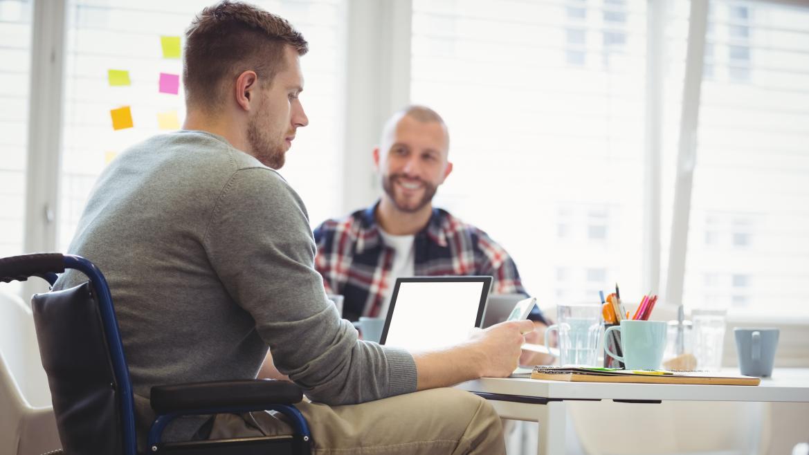 Dos hombres, uno en silla de ruedas, trabajando juntos