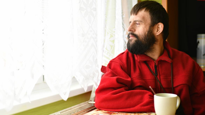 Un hombre con sindrome de Down mirando por una ventana