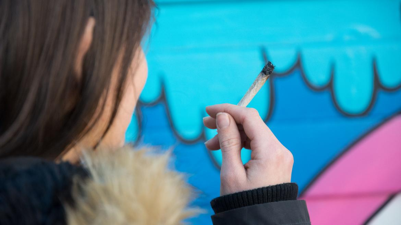 Una joven sostiene un cigarro de cannabis
