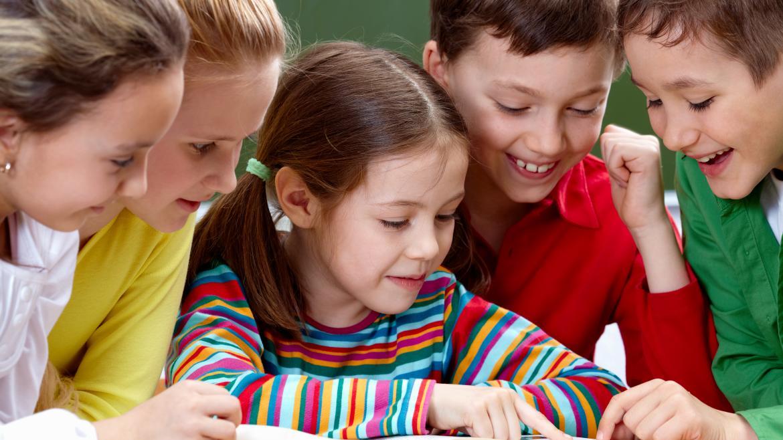 Grupo de cinco niños leyendo alrededor de un libro
