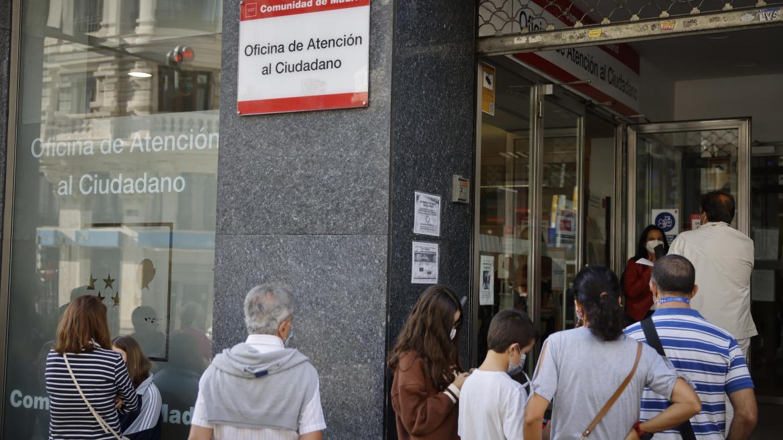 Imagen de la entrada de la Oficina de Atención al Ciudadano de Gran Vía con personas esperando a las puertas