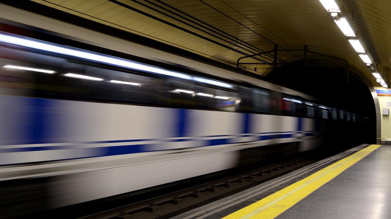 Un tren de Metro en movimiento al pasar por una estación