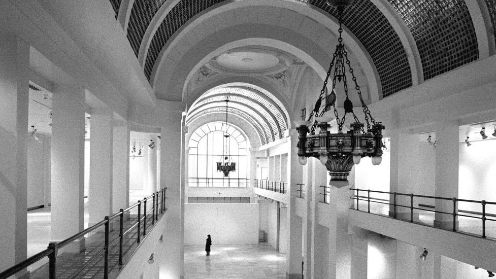 Amplia sala a dos alturas de la que cuelgan grandes lámparas antiguas