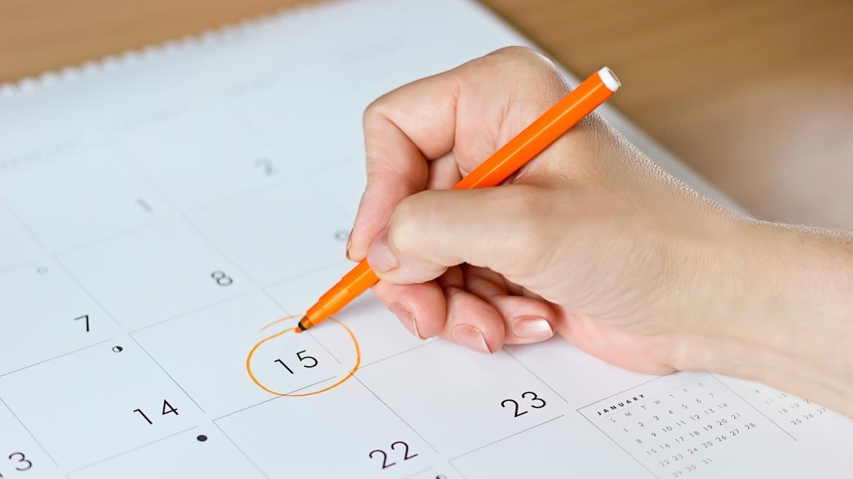 Mano de mujer señalando día de un calendario