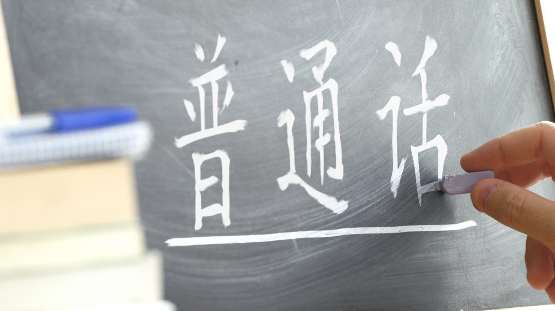 """Una mano escribiendo las palabras """"chino mandarín"""" en chino"""
