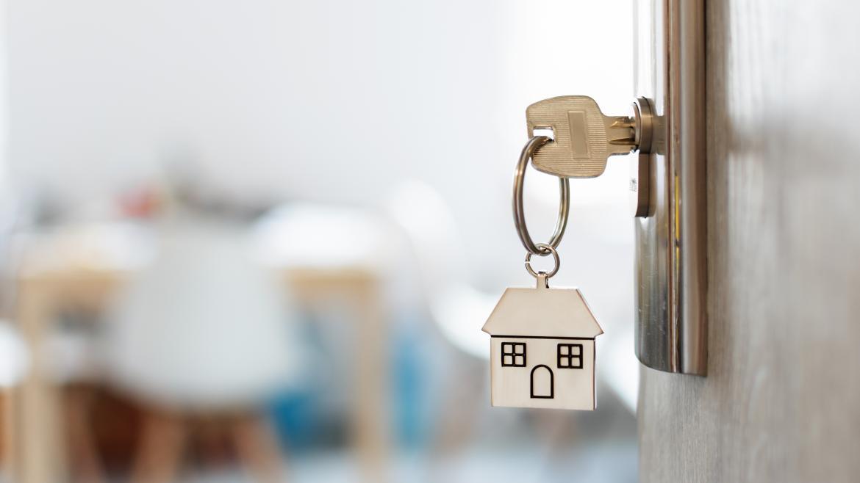 Llave colgando de una puerta con un llavero de una casa